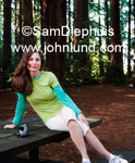 A woman with a video camera or camcoder sitting on a park table in the redwood forest surrounded by huge trees. She has long brown hair, a green blouse, and white capris.